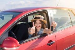 Kierowca kobieta ono uśmiecha się pokazywać nowych samochodów klucze i samochód Fotografia Stock