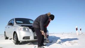 Kierowca kopie out samochód z łopatą od śniegu zbiory