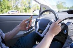 Kierowca texting na telefonie podczas gdy jadący Zdjęcia Stock