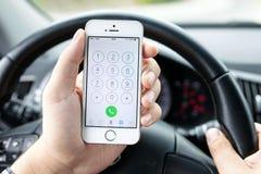 Kierowca w samochodzie wybiera numer numerowego iphone 5s złoto Fotografia Stock