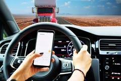 Kierowca wyszukuje smartphone podczas gdy na drogowym wzrastający ryzyko wypadek obraz royalty free