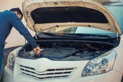 Kierowcy czeka nafciany poziom w samochodowym silniku, patrzeje pod jego samochodowym kapiszonem dla bezpiecznego utrzymania i je zdjęcia royalty free