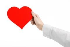 Kierowej choroby i zdrowie temat: wręcza lekarkę trzyma kartę odizolowywająca w postaci czerwonego serca w białej koszula Obrazy Royalty Free