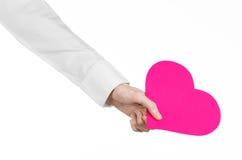 Kierowej choroby i zdrowie temat: wręcza lekarkę trzyma kartę odizolowywająca w postaci różowego serca w białej koszula Zdjęcie Royalty Free
