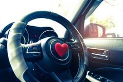 Kierownica z kierowym czerwonym przedmiotem Miłości pojęcia samochodowy pomysł inter obrazy royalty free