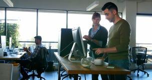 Kierownictwa dyskutuje nad komputerem stacjonarnym przy biurkiem 4k zbiory wideo