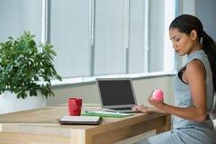 Kierownictwo ćwiczy z dumbbells podczas gdy używać laptop zdjęcia stock