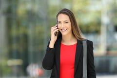 Kierownictwo opowiada na telefonie patrzeje kamerę na ulicie Fotografia Royalty Free
