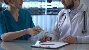 Kierownicza lekarza odmawiania łapówka przy kliniką, żeński stażysta daje pieniądze lekarka zbiory