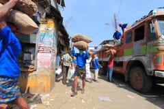 Kierowniczy obciążeniowi pracownicy rozładowywa gunny zdosą od ciężarówki w rynku Obrazy Stock
