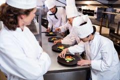 Kierowniczy szef kuchni przegapia innego szefa kuchni dekoruje naczynie Obrazy Royalty Free