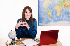Kierownik agencja podróży pije herbaty w miejscu pracy zdjęcie stock