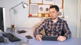 Kierownik firma siedzi przy stołem dokąd pastylka, telefon komórkowy zbiory