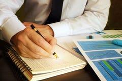 Kierownik pisze pieniężnych dane w księgi głównej książkę Fotografia Royalty Free