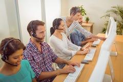 Kierownik pomaga personel w centrum telefonicznym obraz royalty free