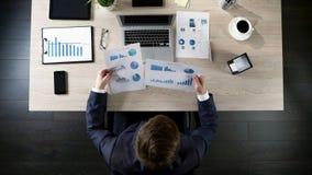 Kierownik porównuje firm statystyki z kierowniczego biura dane na laptopie, odgórny widok fotografia royalty free