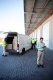 Kierownik pracuje na pastylki i magazynu pracownikach ładuje kartony Zdjęcie Stock