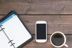 Kierownika dzienniczek i mądrze telefon na drewnianym biurku Zdjęcie Stock