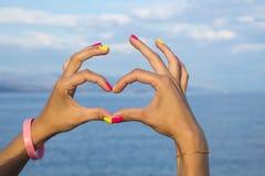 Kierowy kształt robić kobiet ręki przeciw morzu i niebu Obrazy Stock
