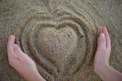Kierowy kształt robi rękami od piaska na plaży Odgórny widok Fotografia Stock