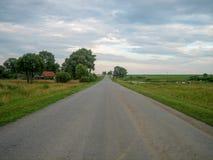 Kieruje asfaltową drogę przez wsi pod niebem, na którym unoszą się chmury zdjęcia stock