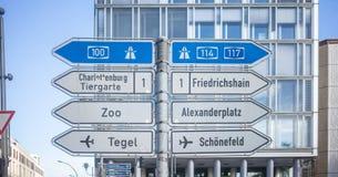 Kierunkowskazy z strzałami pokazują głównych kierunki Berlin, Niemcy Niebieskiego nieba i budynku tło obraz royalty free