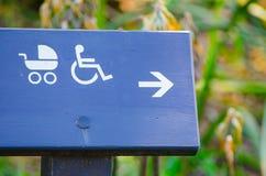 Kierunku znak dla wózka inwalidzkiego i pram dostępnych, na zmroku - błękitny szalunek zdjęcia stock