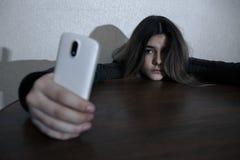 Kies droevige tiener uit die een mobiele telefoon houden betreurend zitting op het bed in haar slaapkamer met een donker licht royalty-vrije stock afbeeldingen