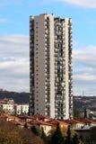 Kies hoge wolkenkrabbers uit toenemend boven veelvoudige familiehuizen en kleinere gebouwen aan kant van kleine heuvel die met be royalty-vrije stock afbeeldingen