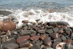 Kiesel auf dem Strand, der durch Welle gewaschen wird Stockbilder