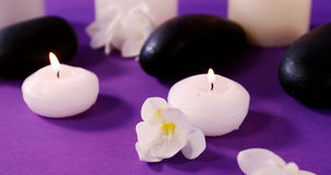 Kiesel, Blumen und Kerze auf Tabelle stock video footage