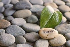 Kiesel gedruckt mit einem Liebeswort Stockbild