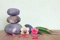Kiesel gestapelt auf eine Zenlebenmode auf einem hölzernen Bambusbrett mit einer rosa Blume und einer Orchidee auf einem grünen H Lizenzfreies Stockbild