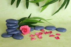 Kiesel gestapelt auf Zenlebenmode mit einer rosa Blume auf Grün und Laubhintergrund Stockbilder