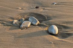 Kiesel im Sonnenuntergang des Sandes in der Dämmerung stockfotografie