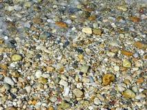 """Kiesel und Gischt auf dem Strand †""""Hintergrund Lizenzfreie Stockbilder"""