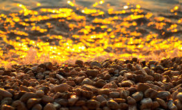 Kiesel und Meer am Sonnenuntergang Lizenzfreie Stockfotos