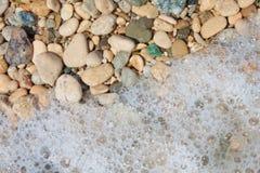 Kiesel und Schaumgummi auf dem Strand, Abschluss Lizenzfreie Stockfotos