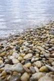 Kiesel und Steine an einem Ufer Stockfotos