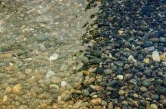 Kieselsteine in das Wasser stockbild