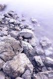 Kieselsteine durch das Meer Seidige Wellen von blauem Meer von der langen Belichtung Lizenzfreies Stockfoto
