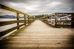 Kiesiger hölzerner Pier an einem bewölkten Tag Lizenzfreies Stockfoto