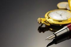 Kieszeniowego zegarka i atramentu pióro na czerni Zdjęcia Stock