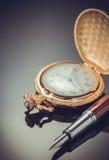 Kieszeniowego zegarka i atramentu pióro na czerni Zdjęcia Royalty Free