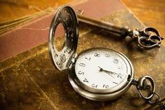 Kieszeniowego zegarka klucz i stara książka Fotografia Stock