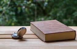 Kieszeniowy zegarek i książka obrazy stock