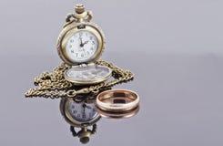 Kieszeniowy zegarek i złocista obrączka ślubna Zdjęcia Stock