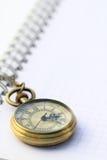 Kieszeniowy zegarek na białej notatnik stronie Fotografia Stock
