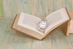 Kieszeniowy zegarek nad wiek książki tłem, czas zdjęcie stock