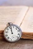 Kieszeniowy zegarek obok książki Obraz Stock